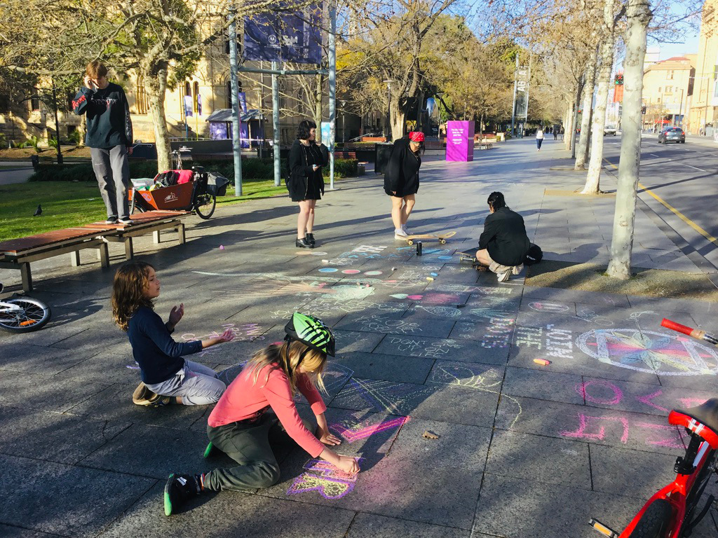 children and teenagers chalking dotzero, pictures and messages of hope on city pavement