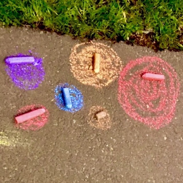 colourful chalk dots with sticks of pavement chalk sitting on them. Pathway and grass.