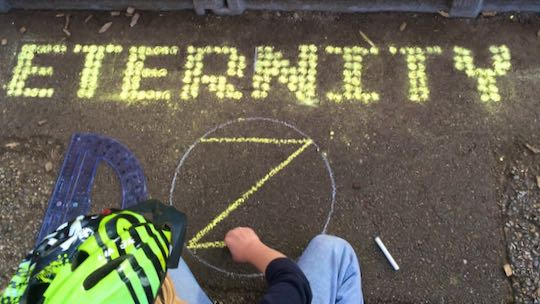 Example: Eternity written in chalk DOTS. Child drawing dotZero in foreground.