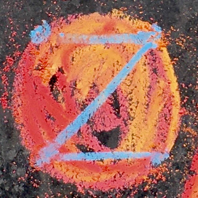 fiery red and ice blue dotZero symbol roughly scrawled in chalk